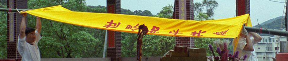 A photograph of two men moving large yellow banner with red writing on it on a large pole used to for Taiwan Photogallery Set J